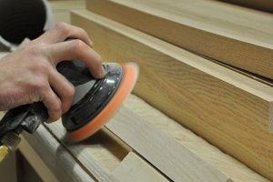 Photo of an employee sanding a stair.